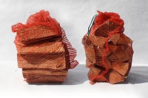 Brennholz in kompakte Netzsäcke